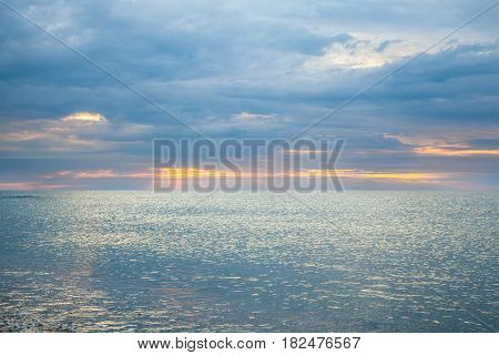 Calm sea in the early cloudy morning. Sunrays radiating from behind the clouds.