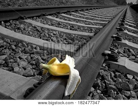 Banana peel on railway. Train Sabotage humoristic conceptual image.