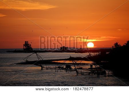 Vibrant sunset on ocean with silhouette of ancient Chinese fishing nets in foreground.
