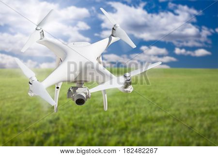 Unmanned Aircraft System (UAV) Quadcopter Drone In The Air Over Grass.