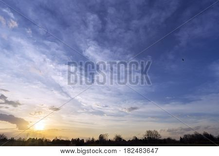 Community park and houses sleeping under a wide sunrse dawn large skyscape with space for text silhouette along bottom