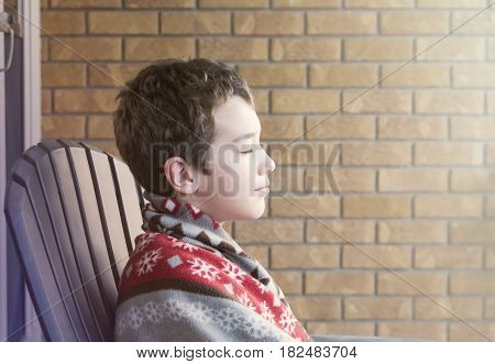 Young boy sitting on porch eyes closed wrapped in blanket enjoying the sunrise peaceful expression