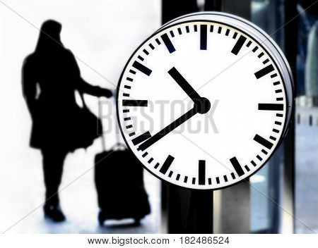 Station clock and a passenger waiting with baggage close up image