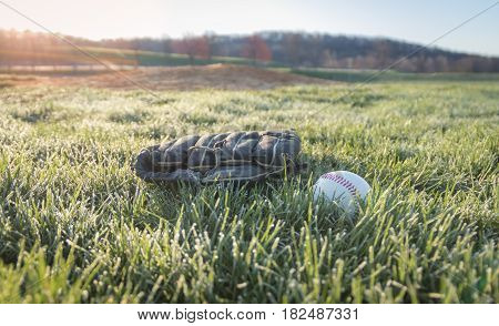 Baseball glove and baseball on large grass field in morning dew as sun rises over mountain