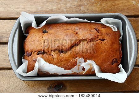 Top view of homemade Banana bread with chocolate chips in a loaf pan on a wooden table.
