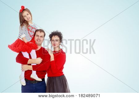 Happy young family dad mom and a little girl in bright red outfits . Dad holds daughter on hands.On the pale blue background.