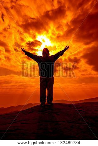 Silhouette of woman with hands rise up and pray with sunlight on orange sky. Christian praise on hill thanksgiving day background. Freedom and vigorous or powerful concept.