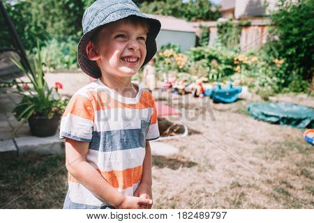 Portrait of cute Caucasian boy wearing stripped tshirt and hat with funny face expression outside on house backyard on summer day smiling laughing in excitement