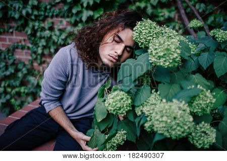 Conceptual art portrait of beautiful handsome young middle east brunette man with long hair and beard in blue hoodie with closed eyes sitting dreaming in orchard among flowers outside