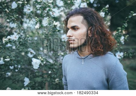 Conceptual art portrait of beautiful handsome young middle east brunette man with long hair and beard piercing in ears wearing blue hoodie looking away among flowers outside