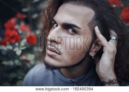 Conceptual art portrait of beautiful handsome young middle east brunette man with long hair and beard piercing in ears wearing blue hoodie looking in camera among flowers outside