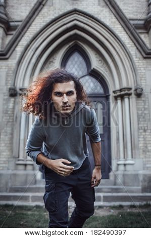 Conceptual spooky weird art portrait of beautiful handsome young middle east brunette man with long hair and beard in grey hoodie looking in camera church on background