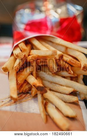French fries potato chips in red paper cup closeup macro shot. Unhealthy fried meal in fast food restaurant