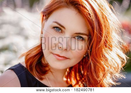 Closeup portrait of middle aged white caucasian woman with waved curly red hair with blue eyes in black dress looking in camera outside in park beauty fashion lifestyle concept