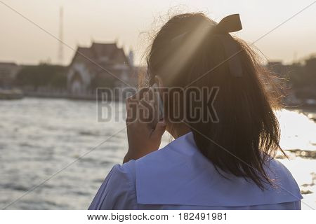 Young woman on cellphone water nature background
