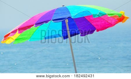 Colorful beach umbrella standing in the sand near the water.