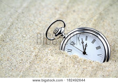 Pocket watch semi buried in the sand , close up image.