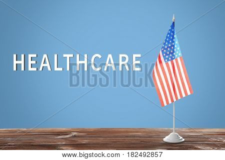 Word HEALTHCARE and USA flag on color background