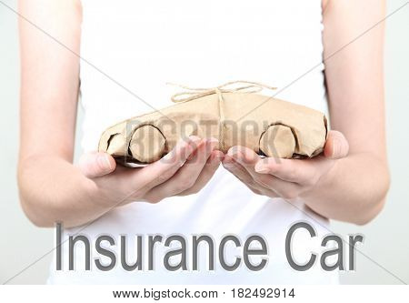 Car insurance concept. Woman holding automobile wrapped in paper