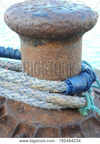 Ship anchor with ropes tied to hold ship in port of call.