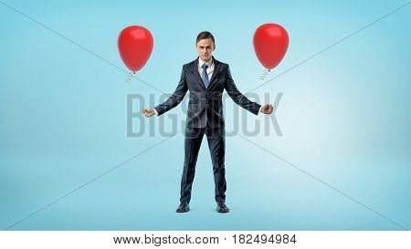 A businessman standing on blue background with a red balloon in each hand. Business and success. Promotions and best offers. Happy occasions.