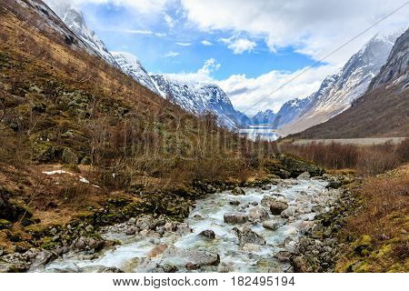 Water flow down from river to lake with snow cap mountain background Norway