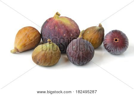 Several varieties of ripe common figs on white background.