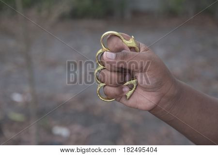 Hand man wearing brass knuckles with selective and soft focus.