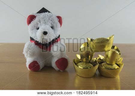 Teddy Bear and gold Chinese on wooden background.