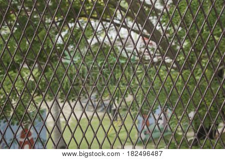 iron chain link fence against the green garden. Soft selective focus and shallow depth of field