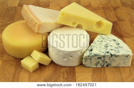 Various cheeses on a kitchen board .
