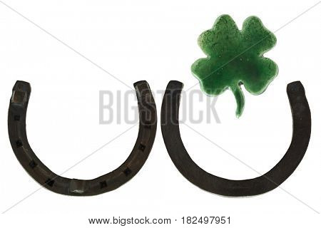 Steel metal horseshoes pointing upwards, green Ceramic Shamrock Four leaf lucky clover as a sign of good luck isolated on white background