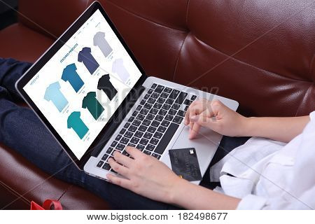 Woman sit on sofa with choosing tshirt on ecommerce webshop