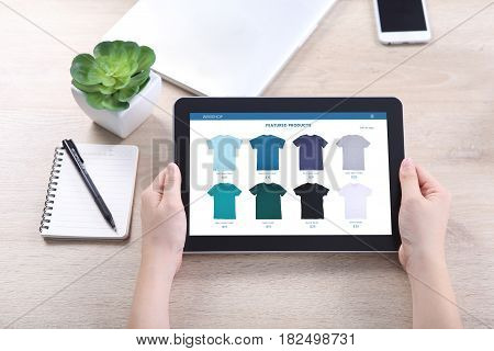 Hand holding tablet with ecommerce webshop on screen