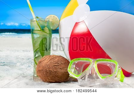Summer vacation with fresh mojito on the seaside. Mask goggles and color ball on a sand on beach background