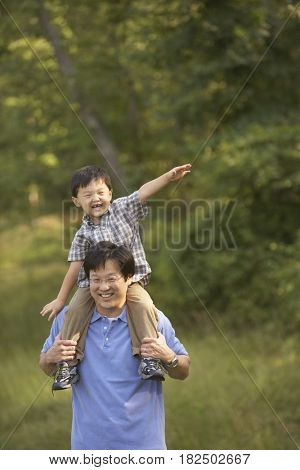 Asian father holding son on shoulders