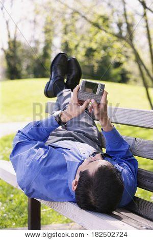 Hispanic businessman using PDA outdoors
