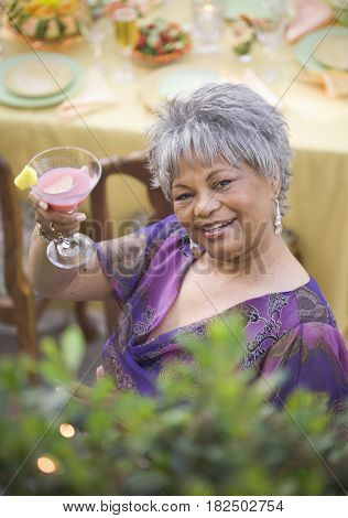 High angle view of senior African woman with cocktail