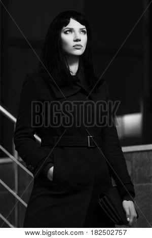 Young fashion woman in black coat walking in city street