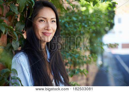 Mixed race Asian woman outdoors looking away, horizontal