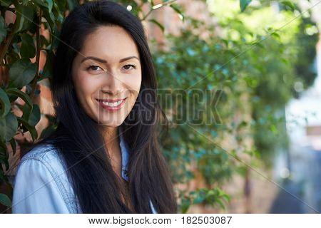 Mixed race Asian woman outdoors looks to camera, horizontal