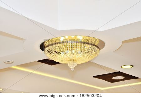 White beautiful chandelier against the white ceiling