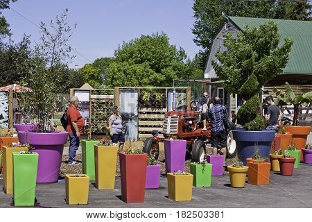 Laval, Quebec - June 14, 2015 - Wide view of people checking out a red tractor in the very colorful Garden Center of the Nature Park, Laval, Quebec on a sunny day in June.