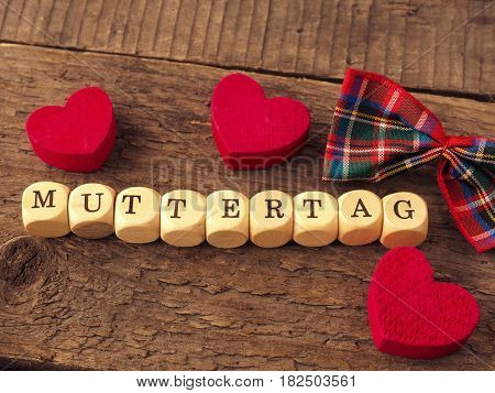 Mothers Day background with the German word Mothersday on wooden dices red heart shapes and bow decoration
