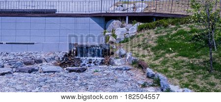 Small waterfall at bottom of bridge with rocky foreground in lakeside park in South Korea
