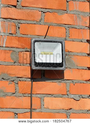 LED flood light spot light on the top house construction site outdoor. Waterproof LED Floodlights Or Lawn Lighting on the Construction Site.