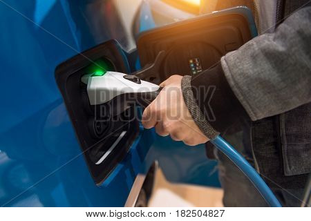 Man charging electro car at charging station. Man holding in hand power cable supply plugged in charging port