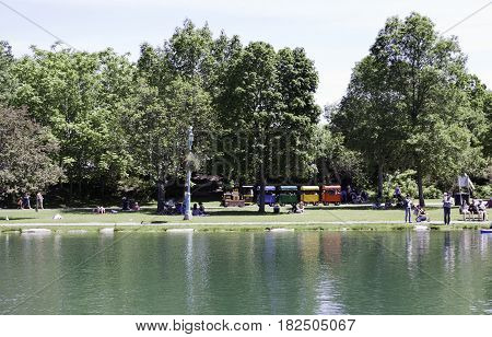 Laval, Quebec - June 14, 2015 -- Wide view of a colorful children's train ride beside a small man made lake and groups of people enjoying the weather in the Nature Park, Laval, Quebec on a sunny day in June.