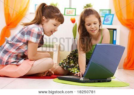 Lächelnd Grundschulkind Schüler Surfen im Internet auf Laptop-Computer zu Hause.?