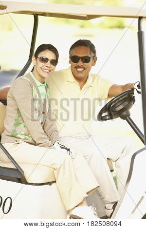 Middle-aged Hispanic couple in golf cart
